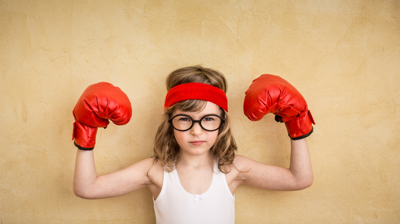 strong kid boxing gloves flexing