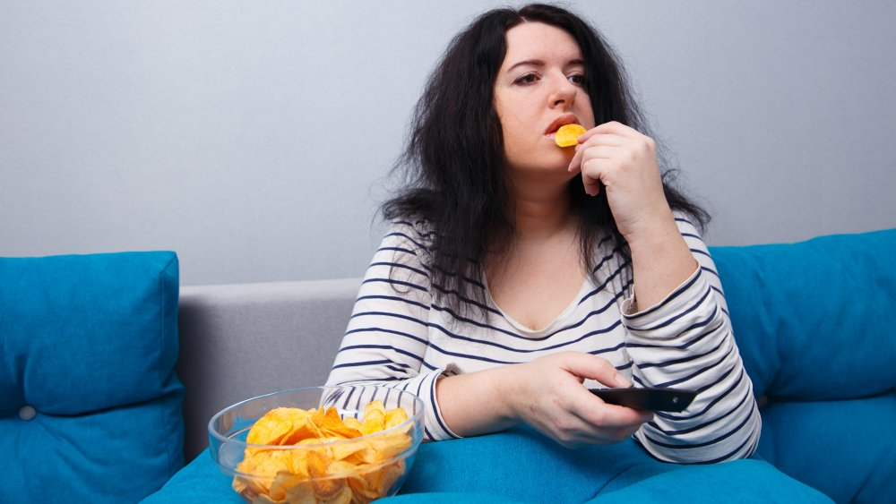 Woman eating potato chips and watching television on the couch