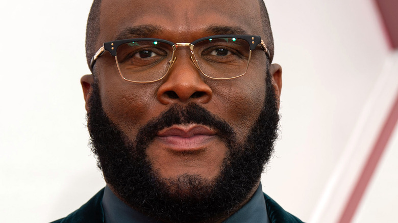 Tyler Perry slight grin with facial hair and glasses