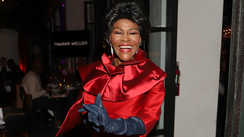 Cicely Tyson smiling in red dress and black gloves