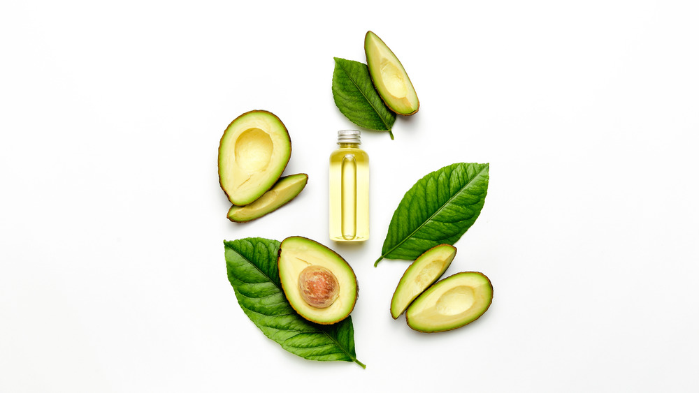 Avocado oil surrounded by avocados