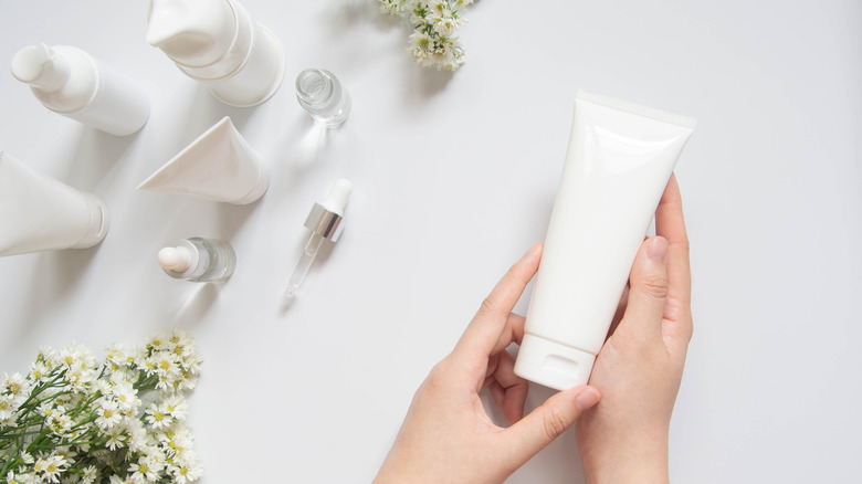 A person holding a tube of lotion