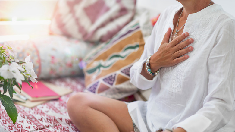 Person sitting and focusing on heart chakra