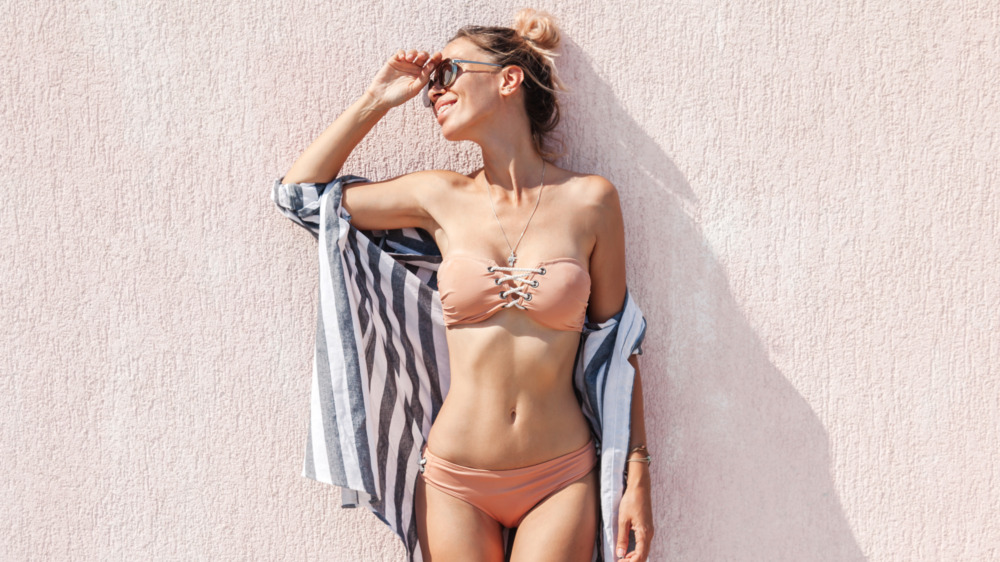 Woman in a bikini poses on a wall