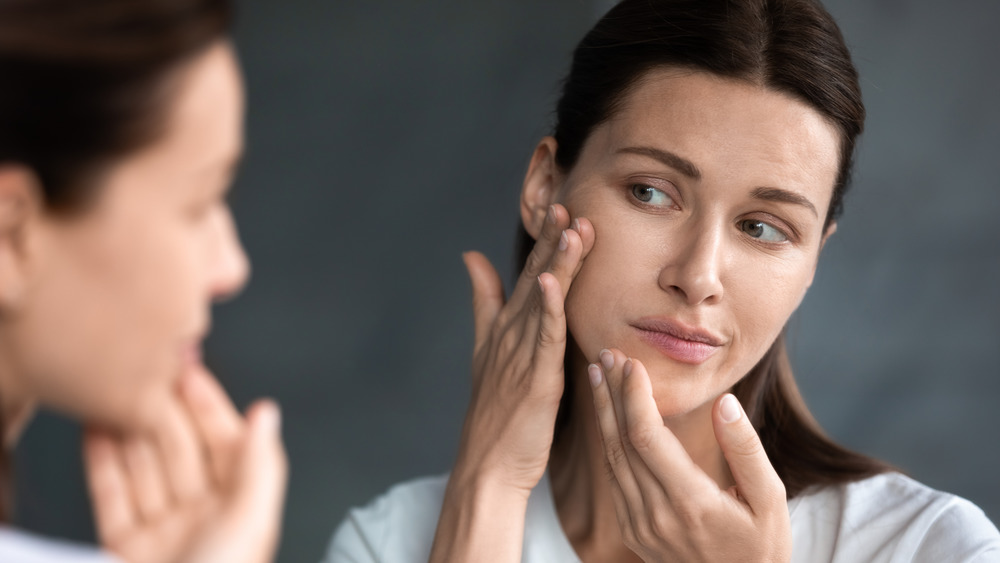 Woman looks at her dry skin in the mirror