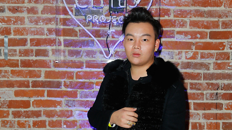 Kane Lim posing in front of wall