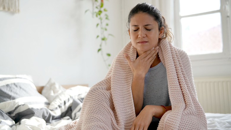 Woman in bed with sore throat