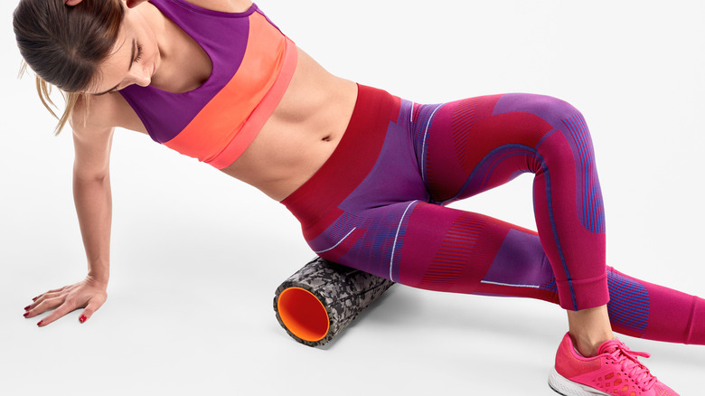 Woman wearing colorful workout clothes using a foam roller on her hip