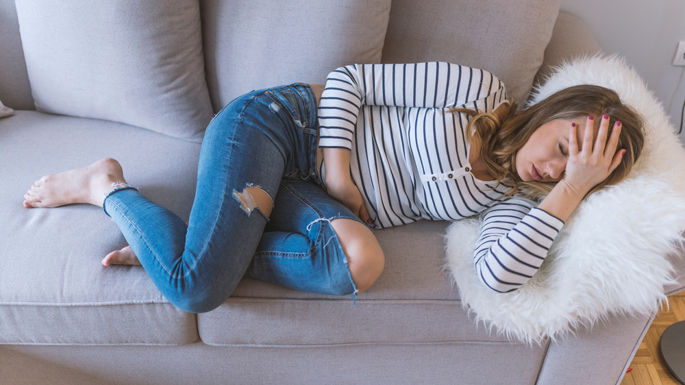 Woman lying down with stomach cramps