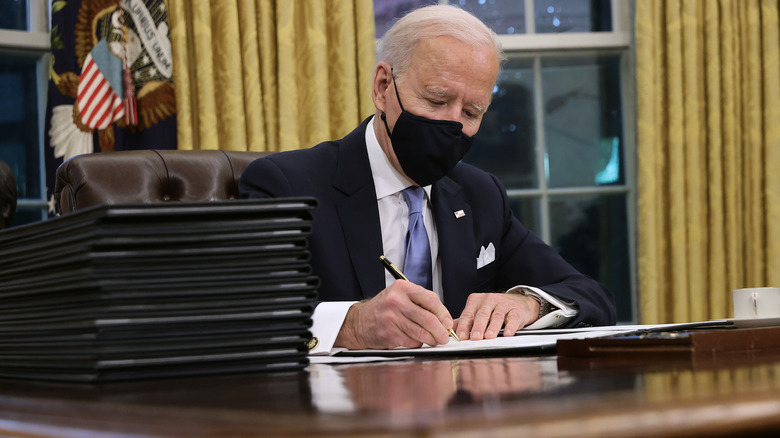 President Biden signing executive orders in mask