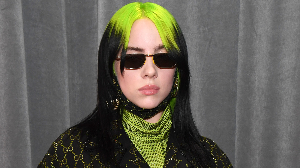 Billie Eilish sporting green hair and sunglasses