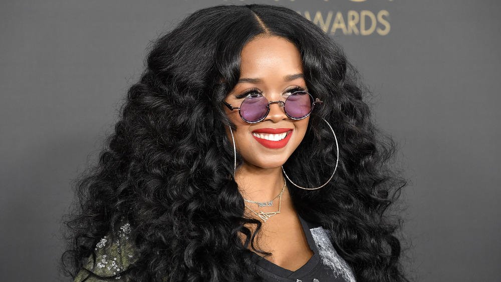 H.E.R. smiling at event, wearing purple-tinted glasses