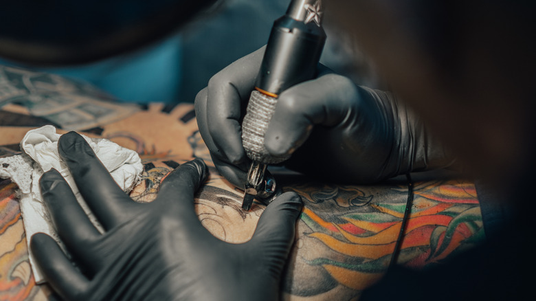 Closeup of tattoo artist wearing gloves and holding equipment tattooing someone's back