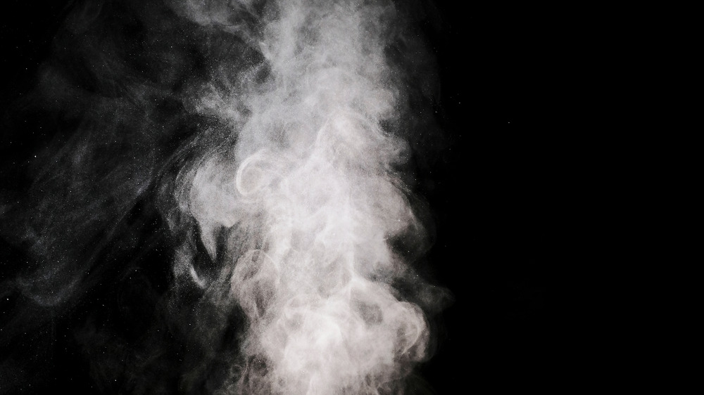 smoke puffing upwards with a black background