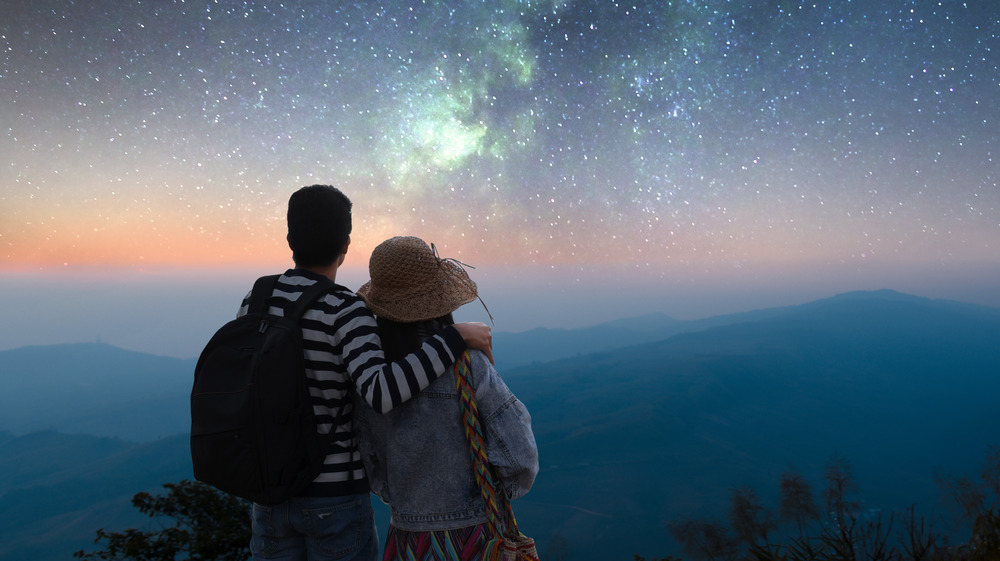 Traveling couple looks out at the stars together