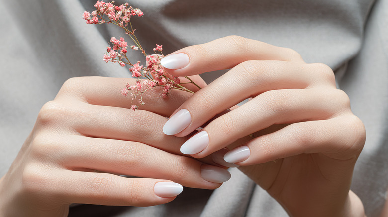 Closeup of woman's fingernails while she holds a pink flower