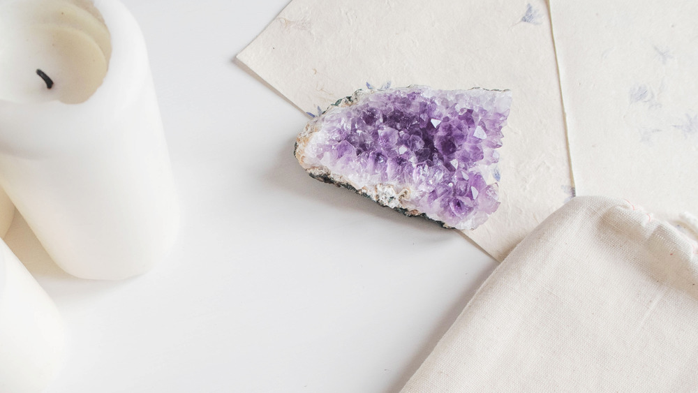 Amethyst cluster, a white candle