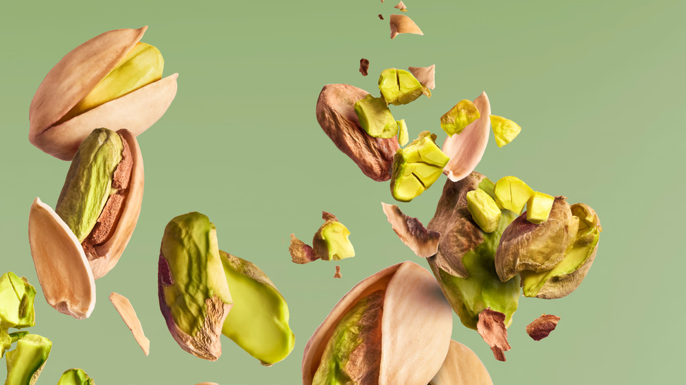 pistachios in there shell with a green background