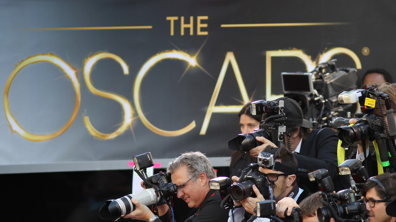 Photographers swarm the red carpet against a backdrop of Oscars signage