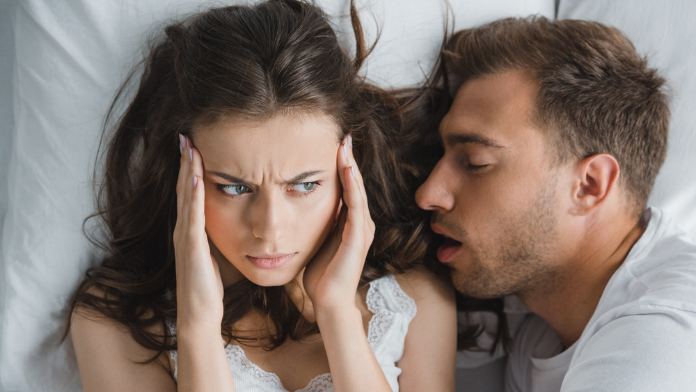 Frustrated woman and sleeping man