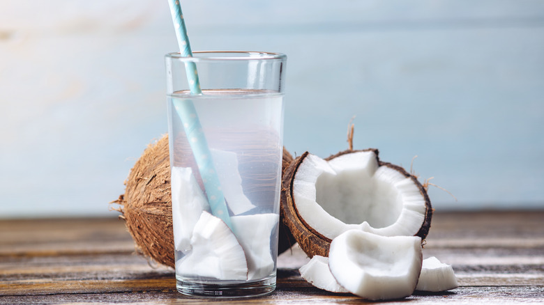 Glass of coconut water with coconut pieces in it