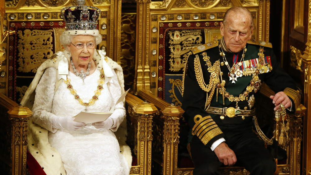 The Queen sits on the throne alongside Prince Philip