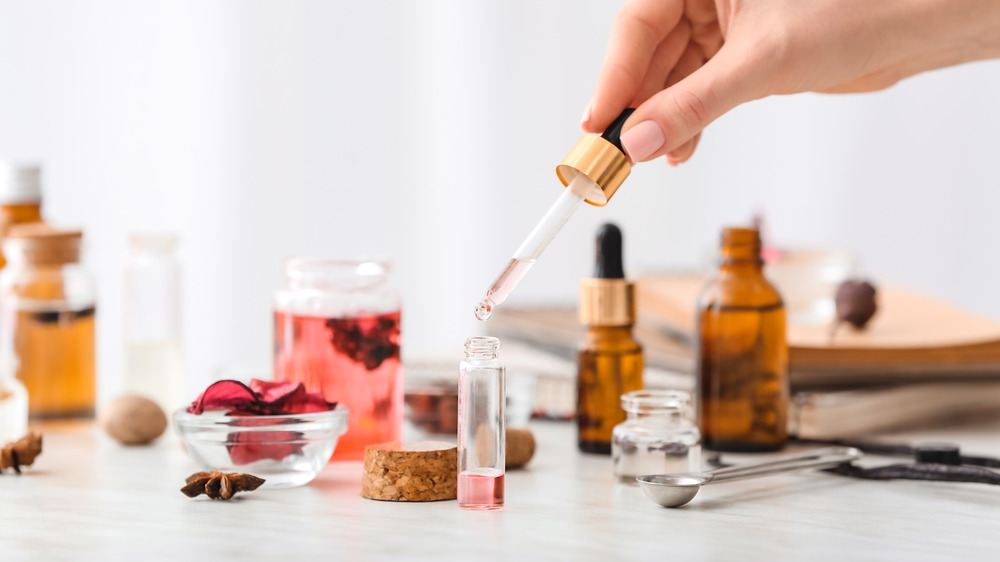 A hand dropping essential oils into a container