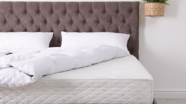A bed with covers and pillows