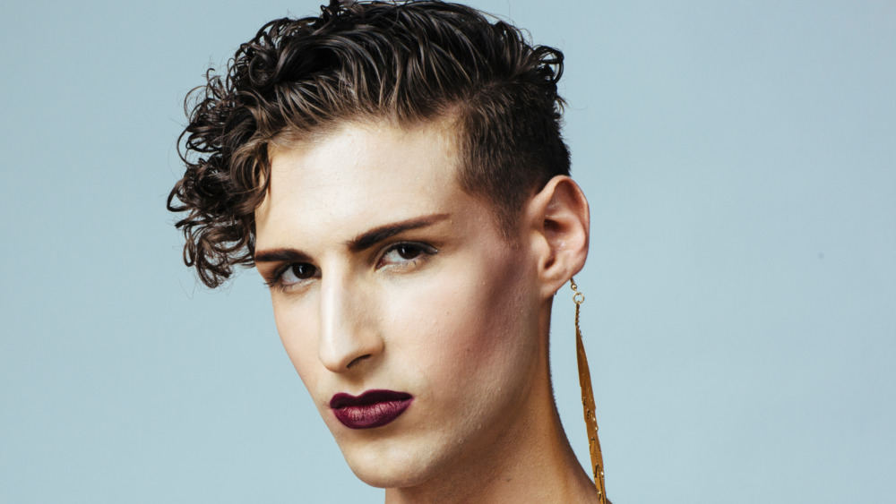 Young man wearing eyeliner, mascara, and lipstick