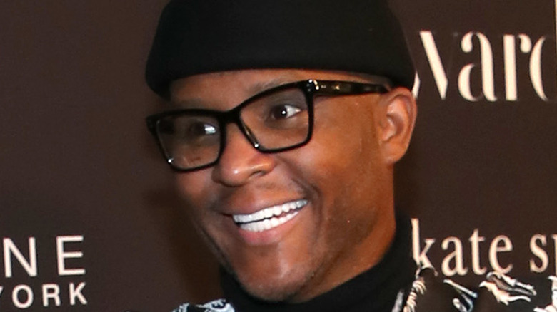 Law Roach wears a black beanie and glasses and smiles.