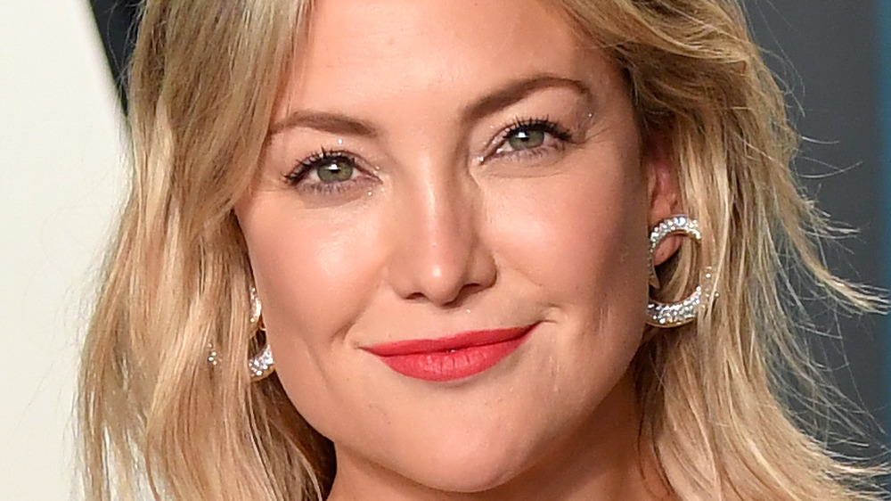 Kate Hudson smiles with red lips and hoop earrings