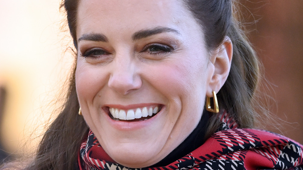 close up of Kate Middleton wearing earrings and red plaid
