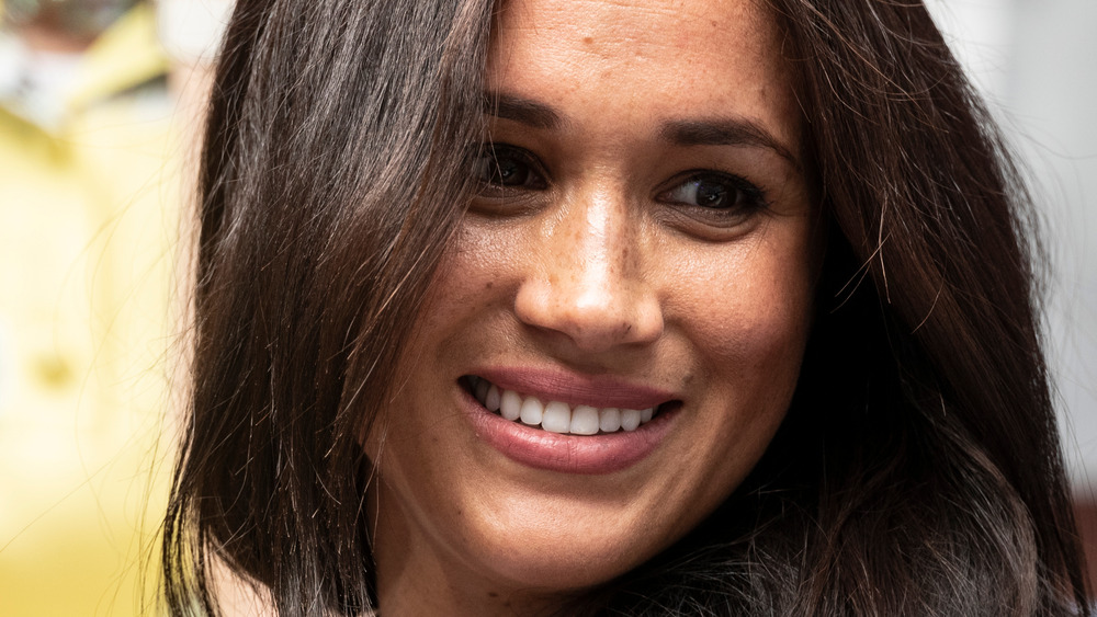 Meghan Markle wears her hair down and smiles
