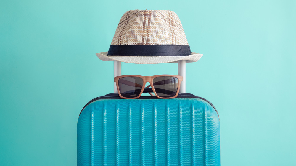 Luggage, sunglasses, and a hat
