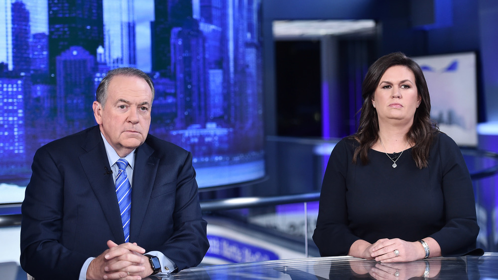 Mike Huckabee and Sarah Huckabee Sanders sitting at desk