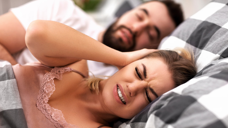 Woman trying to get sleep with a snoring husband