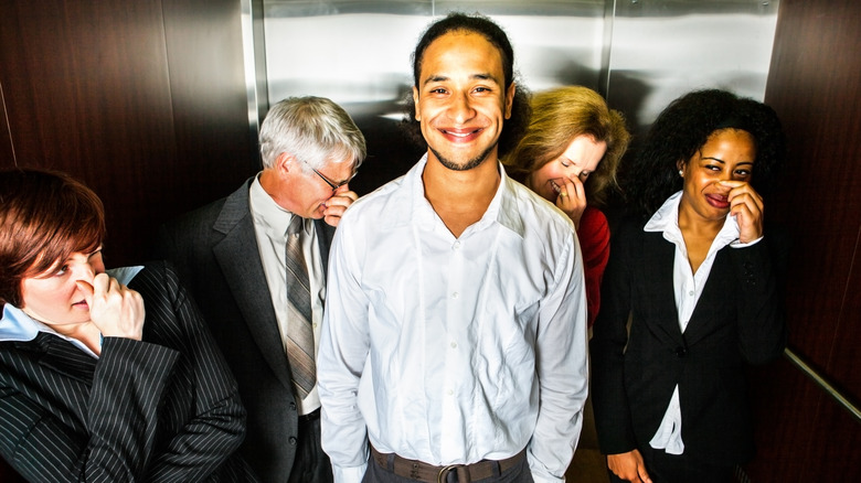 man smiling in elevator as others hold their noses