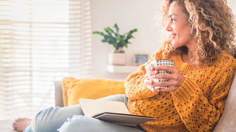 Woman smiling and reading with mug