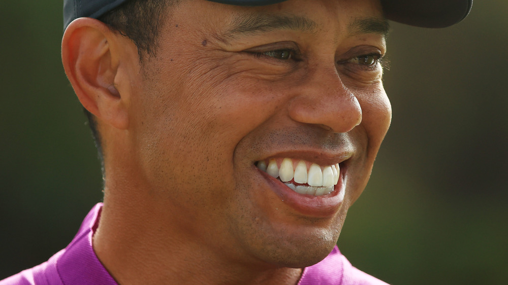 Tiger Woods smiling in purple