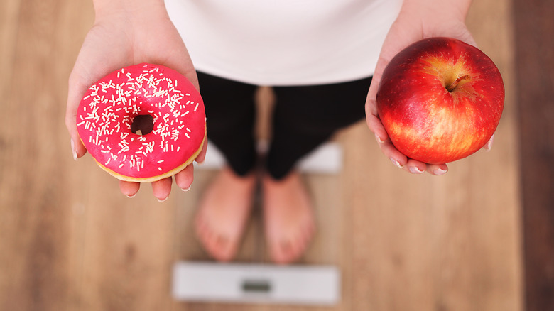 Woman weighing donut vs. apple