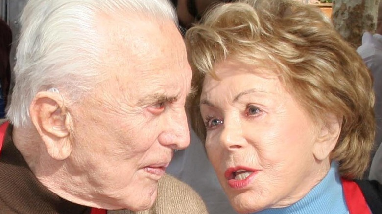 Kirk Douglas and Anne Douglas speaking closely