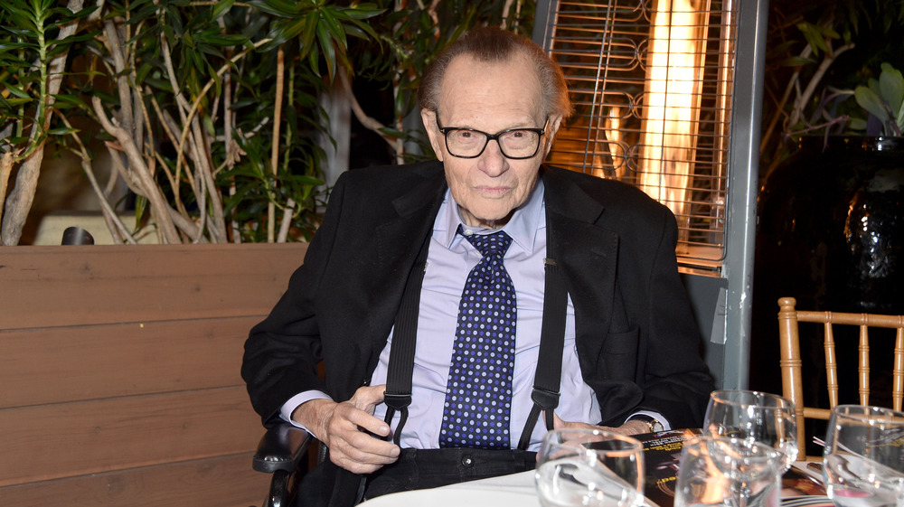 Larry King attends event and smiles