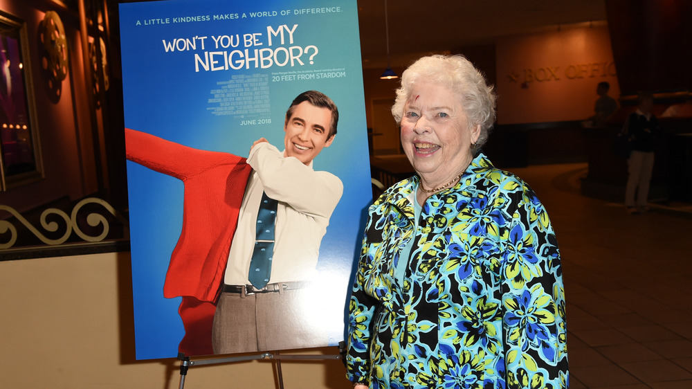 "Mrs Joanne Rogers next to a ""Won't You Be My Neighbor"" poster"