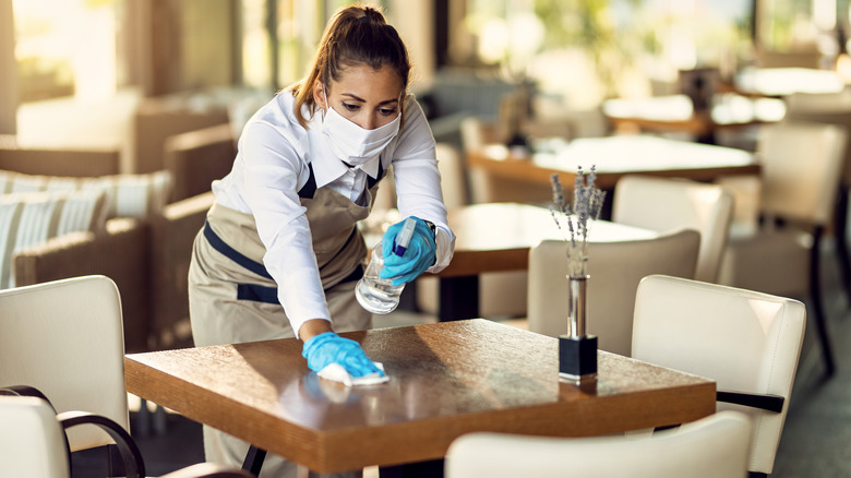 Waitress disinfecting tables while wearing protective face mask and gloves.