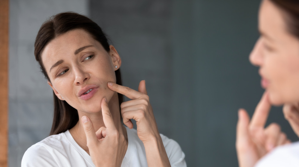 A woman popping a pimple