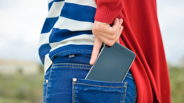Woman with smartphone in pocket