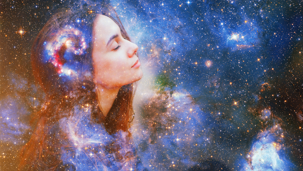 A woman in front of a background full of stars and cosmic images
