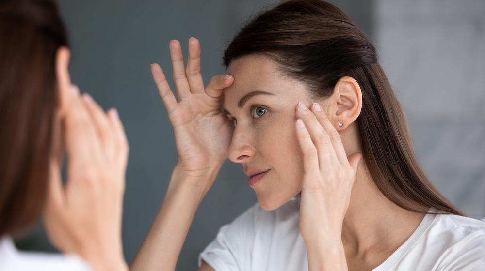 A woman inspects her face in a mirror