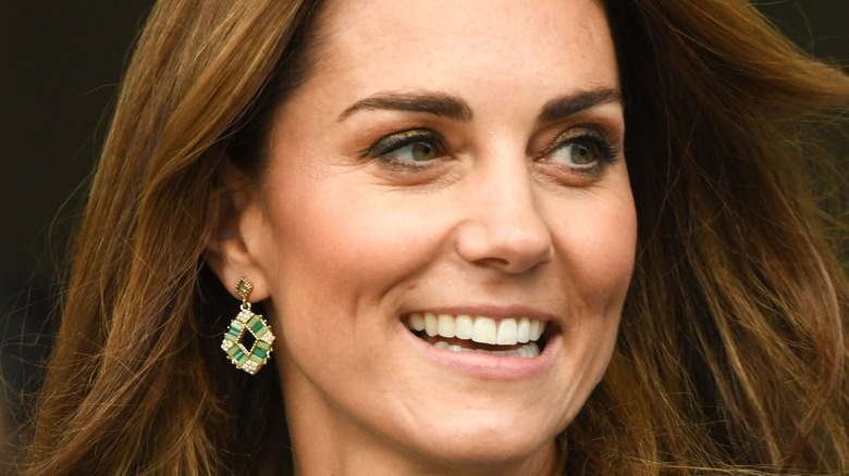 Kate Middleton smiling with hair down and emerald earrings