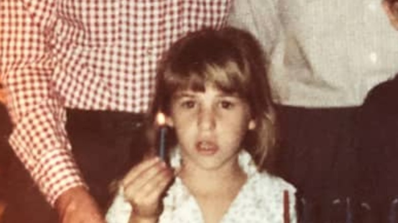 Mayim Bialik as a young girl holding a candle